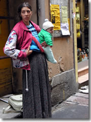 A gypsy woman begging--with an infant for sympathy points--outside a market in Bologna, Italy.